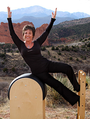 Suzanne on exercise equipment in front of colorado mountains